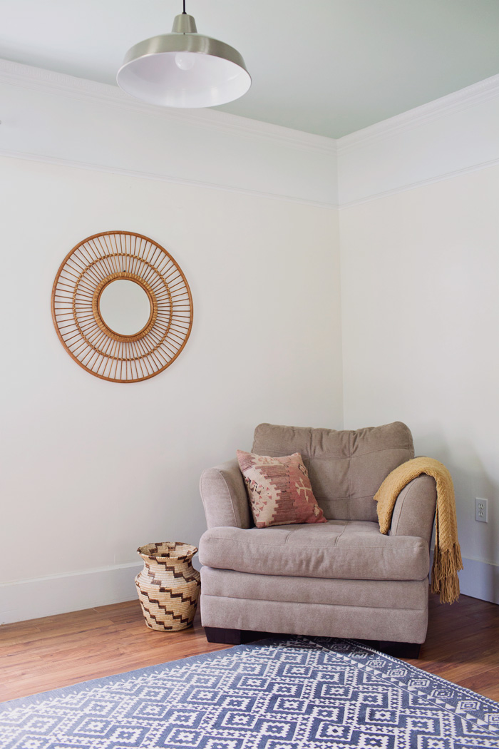 Boho sitting area in home office with beige armchair and kilim pillow