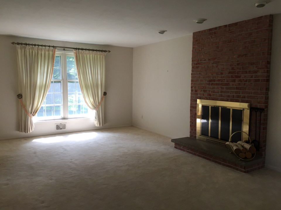 White Living Room with White Carpet and Brick Fireplace