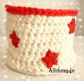 Cesto de trapillo blanco y borde rojo, con estrellas de ganchillo rojas.