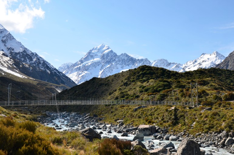 Mt Cook sits in the sun with the glacial river running through Hooker Valley and a cable bridge.