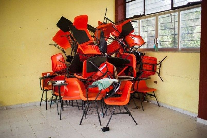Chairs sit in a pile int he corner of a class room that has been cleared out in the Ayotzinapa normalista school, in Guerrero, Mexico, November 16, 2014. Classrooms in the school have been turned into sleeping quarters for visiting students from other schools, family and supporters. (Brett Gundlock/Boreal Collective)