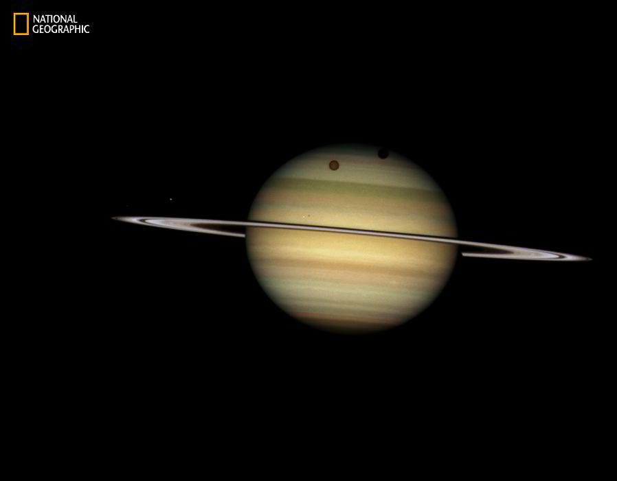 Saturn's Parade of Moons Four moons of Saturn passed in front of their parent planet in this 2009 Hubble image [NASA, ESA, AND THE HUBBLE