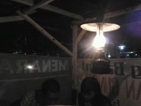 sepasang pemuda makan malam diterangi sinar lampu teplok di warung bakmi jawa, Solo.
