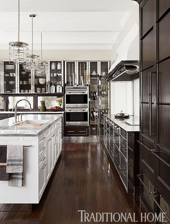 Entertaining Kitchen with Wolf Wall Ovens, Glass Front Cabinetry, Brushed Stainless Steel Cabinetry, Wood Floors & Pendant Lighting by Mick de Giullo
