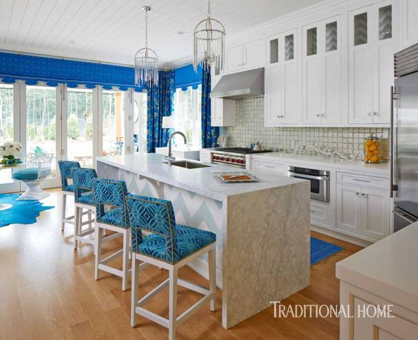 Kitchen Dressed in Vivid Blue Contrasted with White Cabinetry, Frosted Mirror Back Splash Tiles and Pendant Lighting by Hudson Valley Lighting. Marlaina Teich