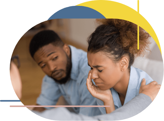 Family mediator at Aligned Choice offers his compassion to comfort a client who is crying, her spouse is close by and looks at her with care.
