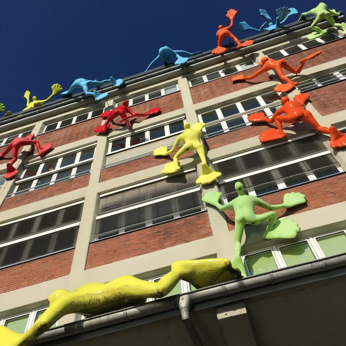 Rosalie's Flossis figures climbing a building in Düsseldorf Mediahafen