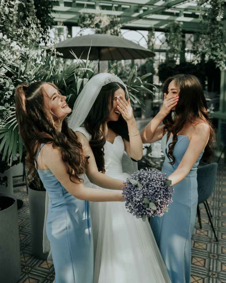 bride holding bouquet of flowers with her bridesmaids