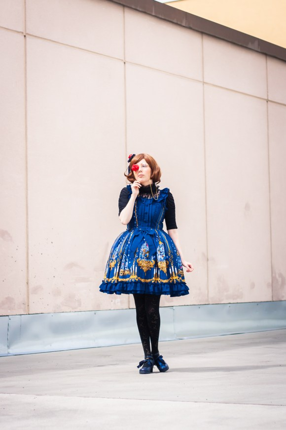Blue dress with black blouse. Golden glasses with roses. Brown wig with blue headbow with roses. Blue shoes and black tights with golden bows.