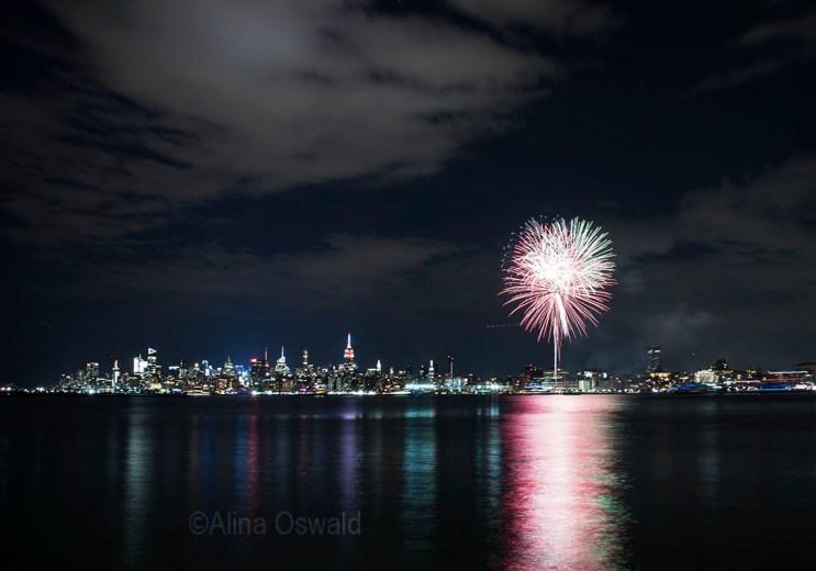 Manhattan skyline at night illuminated by NYC Pride 2017 fireworks. Photo by Alina Oswald.