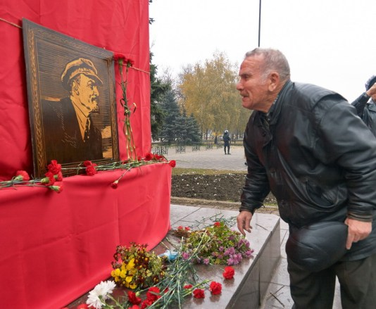 A man lays flowers to a former Lenin's monument