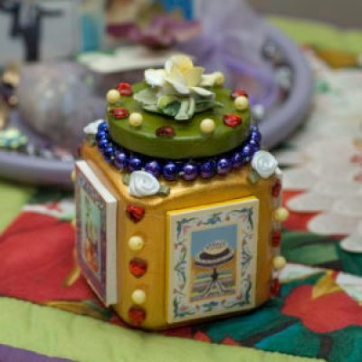 A decorative jar that contains ribbons, beads, images of painted furniture and a porcelain pin on top