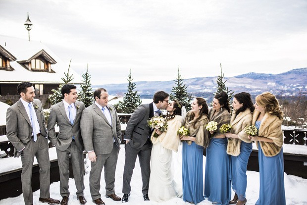 The Bride & Groom share a celebratory kiss while their bridal party looks on