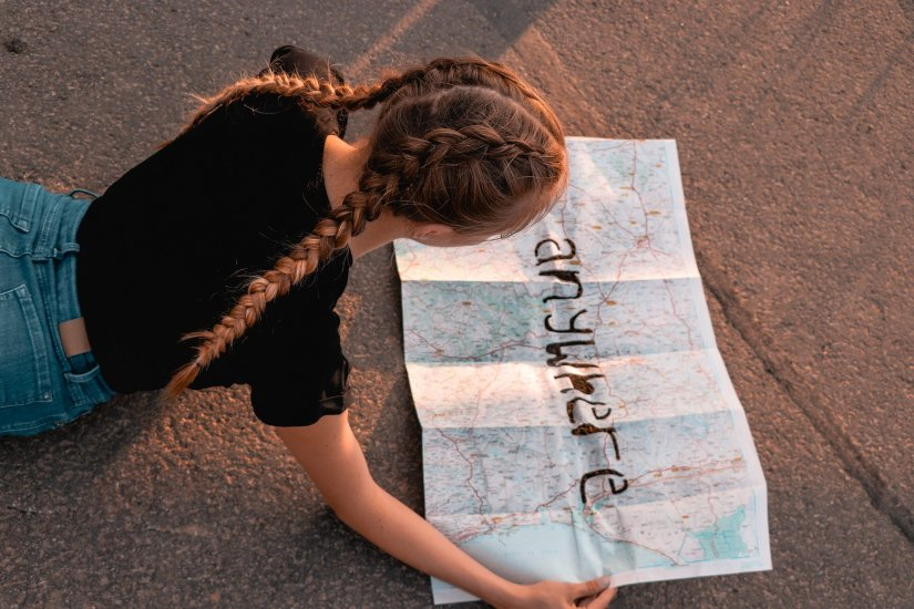 Girl with braids looking at map with anywhere written across it