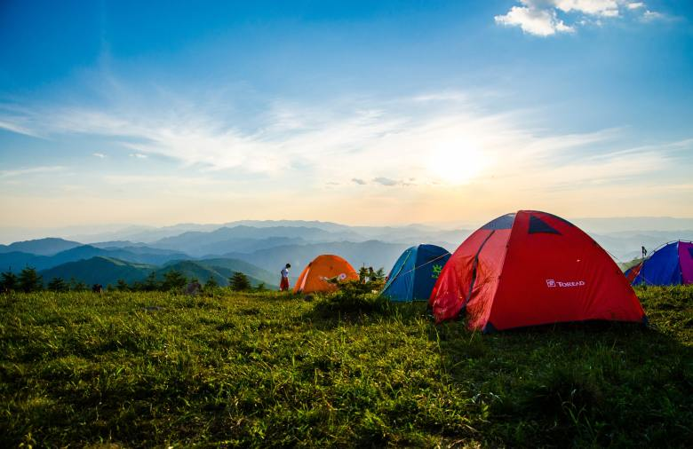 four tents on a field with mountains in the distance representing a family camping trip