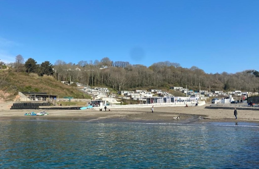 A small beach with hillside villas surrounded by a woodland