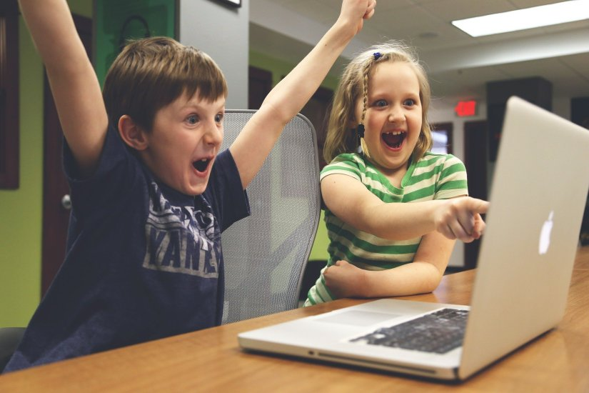 Two children laughing at a laptop