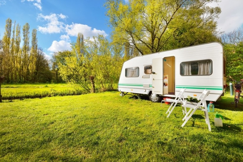 Caravan in field with two white chairs