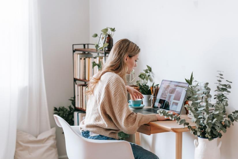 Freelancer working on laptop with photos on screen at home