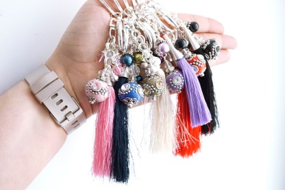 a hand holding asian inspired beaded bag charms