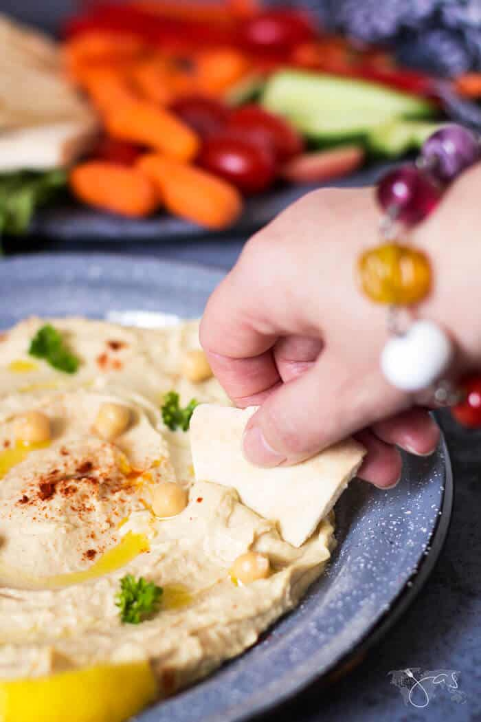 Dipping pita bread into homemade hummus