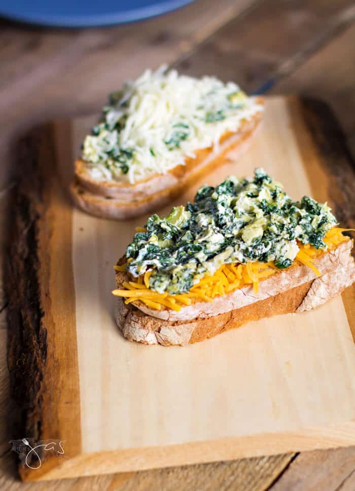 bread slices filled with cheese and spinach artichoke dip ready to be grilled