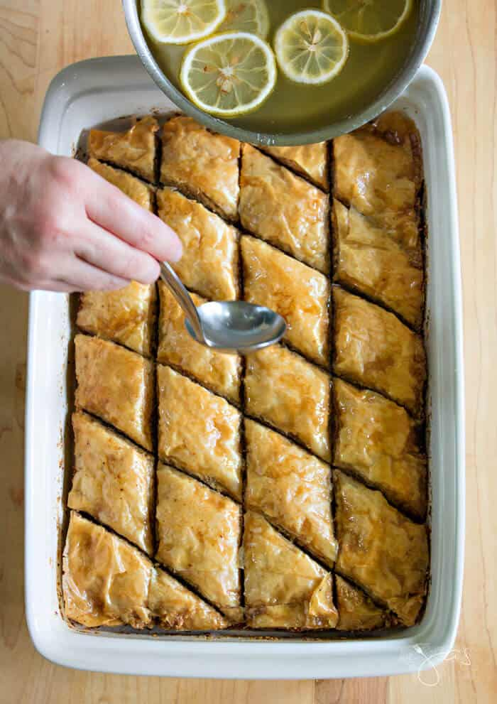 pouring lemony syrup over baklava
