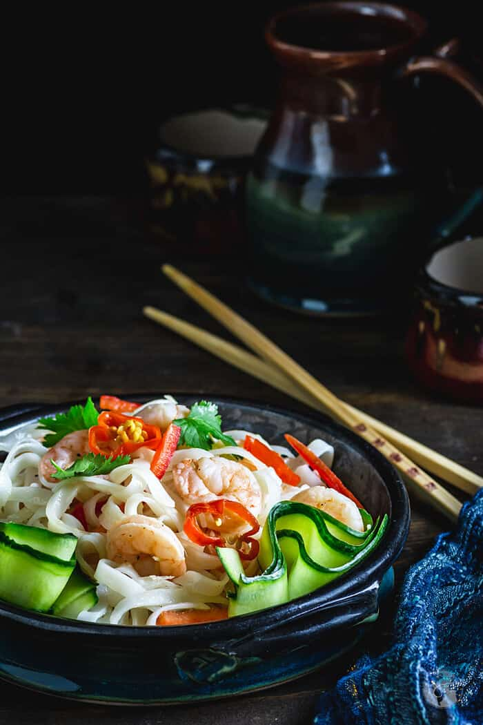 Thai salad with rice noodles in a bowl served with chopsticks.