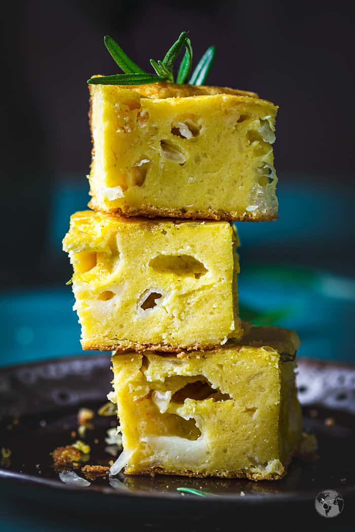 Stacked squares of cheese and onion cornbread with rosemary.