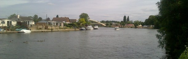 Looking across the Thames at Walton on a summer day, with a boat moving up the river.