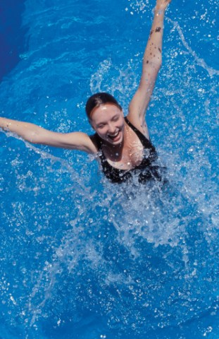 Woman jumping out of swimming pool