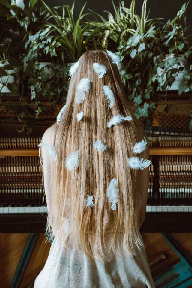 woman with long blond hair with feathers