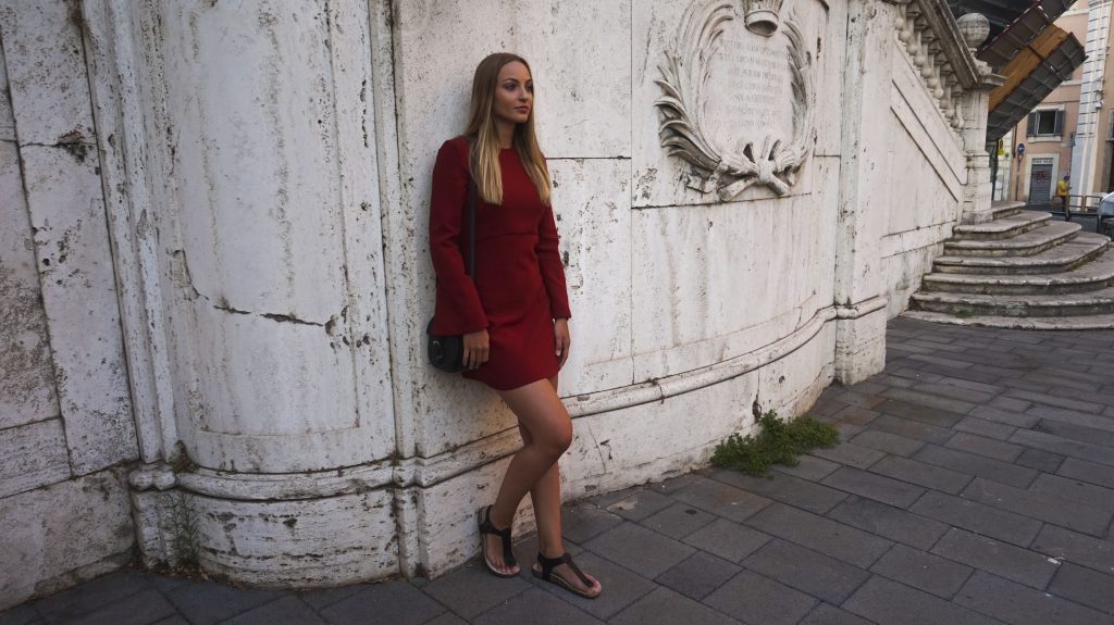 leaning against wall in Rome in the red flared sleeves dress from mango