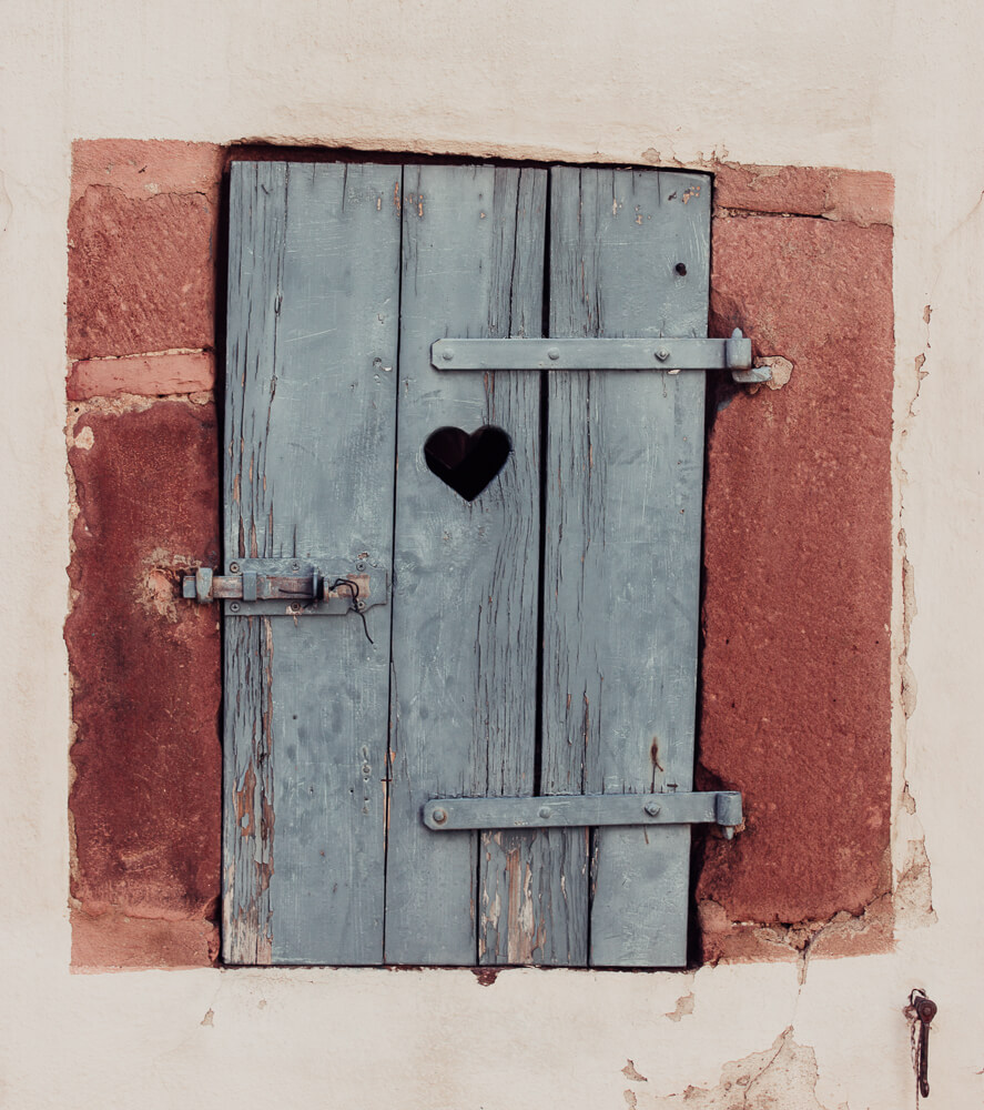 A blue wooden door with a heart shape cut out from it