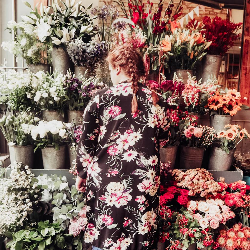 Woman in a floral dress standing in front of a flower stand in Bath UK