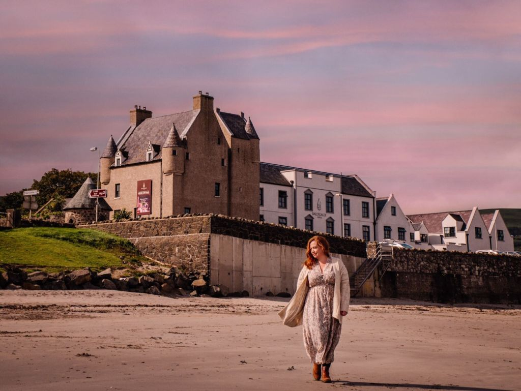Woman walking on the beach in front of Ballygally castle in Antrim Ireland