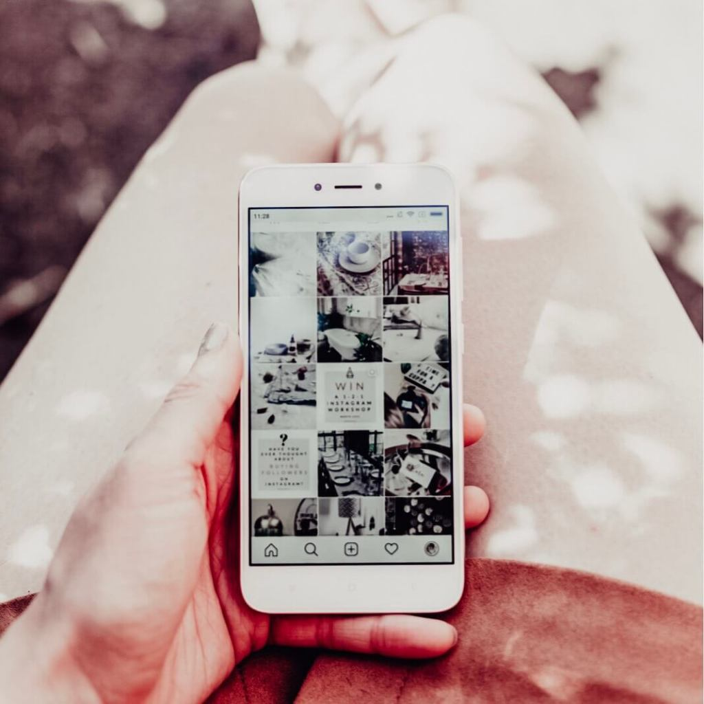 Image of a girl holding her phone open on her Instgram account