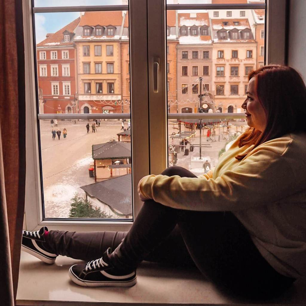 Woman sitting on a windowsill looking out at Warsaw Old town square at Christmas.
