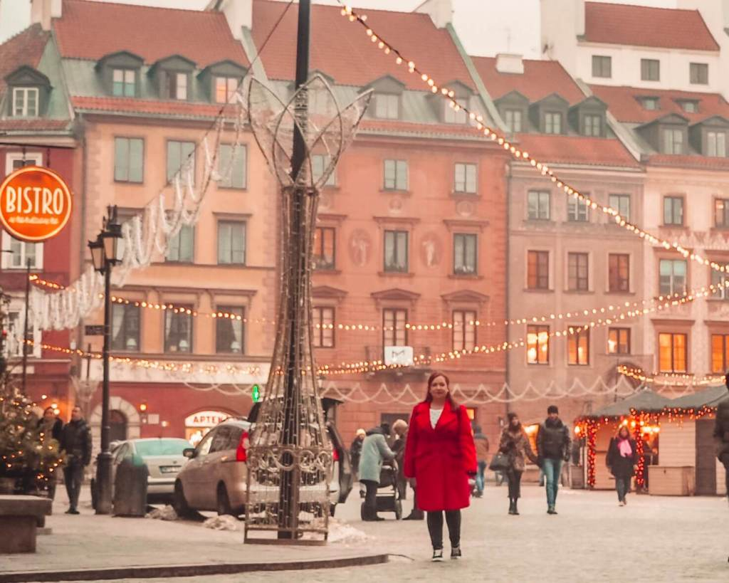 Woman in a red coat walking through Warsaw's old town square at Christmas