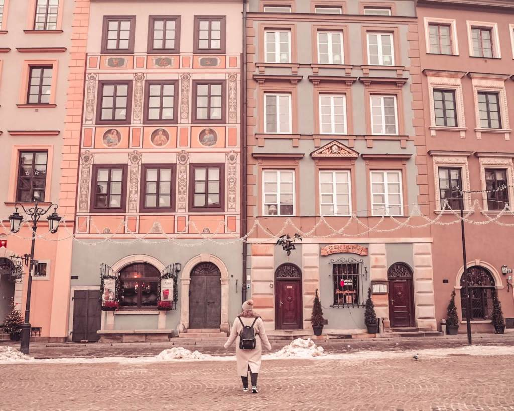 Woman in a beige coat and hat standing in front of the pastel buildings of Warsaw old town square