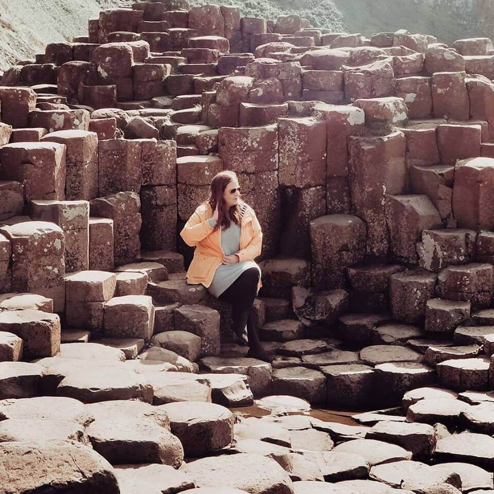 girl sitting on rock at Giant's causeway Northern Ireland