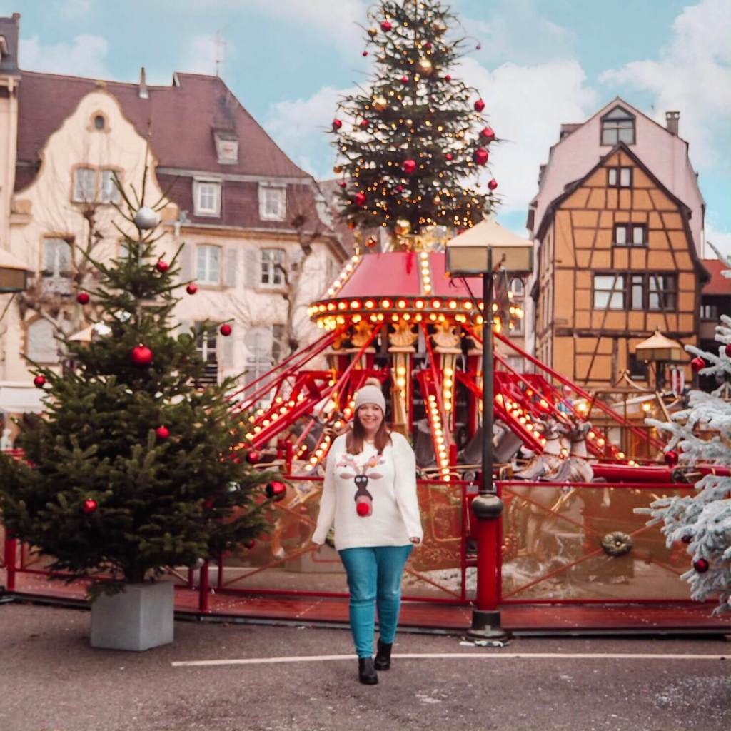 Woman wearing a Christmas jumper in front of a carousel in Colmar Alsace France