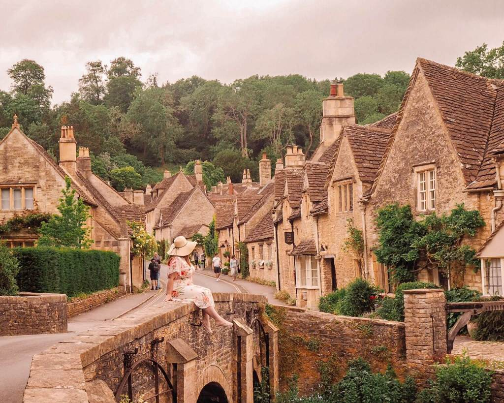 Woman sitting on the bridge in Castle Combe a village you must visit in the Cotswolds