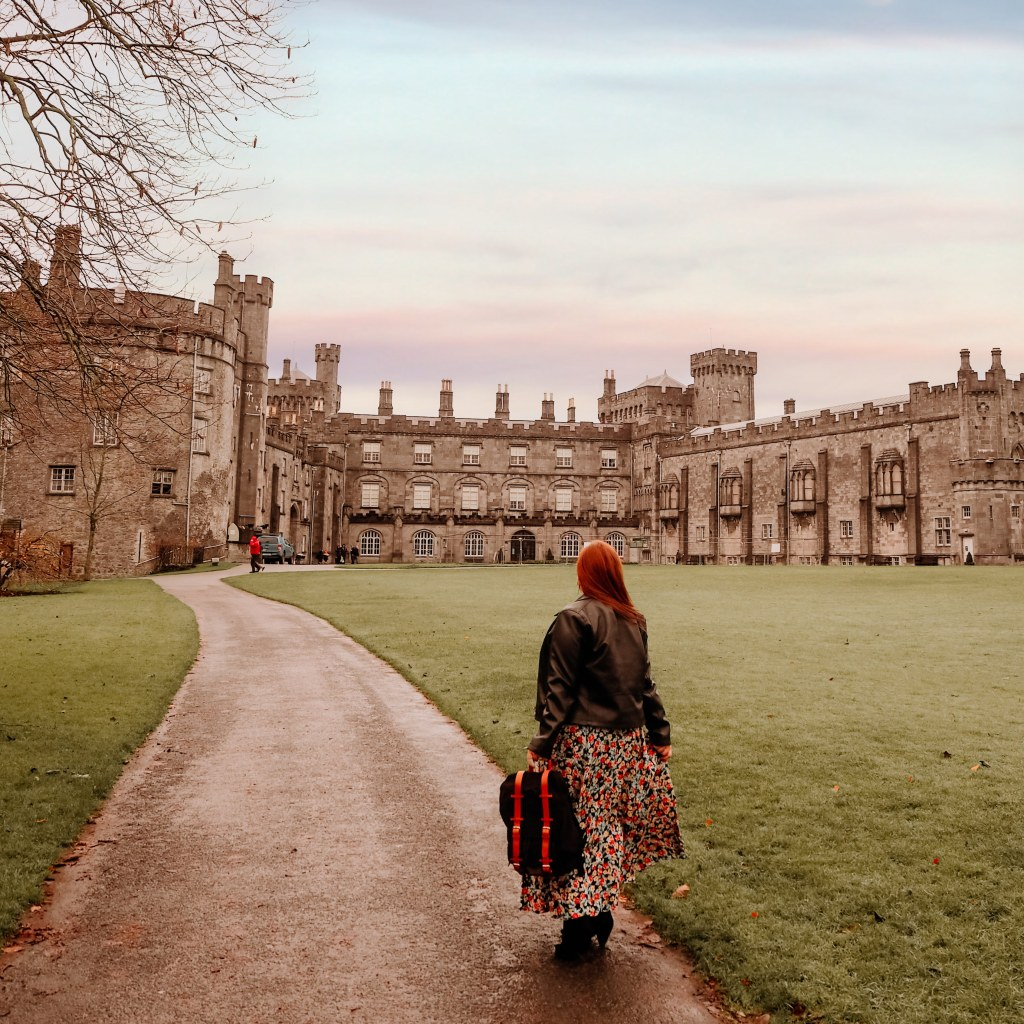 Woman wearing a floral dress and black jacket exploring the grounds of Kilkenny castle