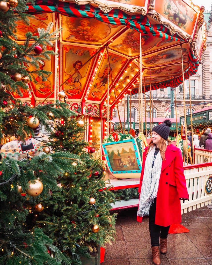 Girl in a red coat at a christmas carousel at the Hamburg Christmas markets