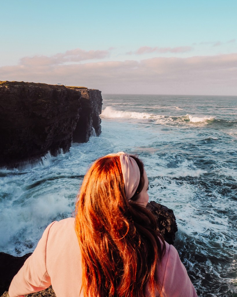 Irish woman with red hair and wearing a pink hairband and coat watching the waves crash in from Kilkee Cliffs