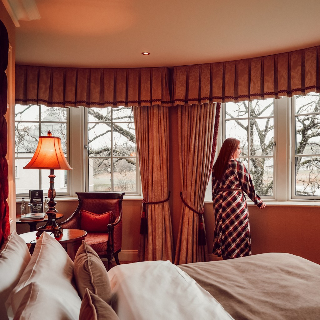 Woman in a checked dress in a luxury hotel room looking out of the window at the view