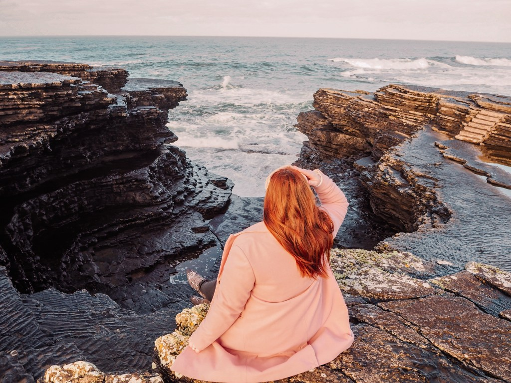 Irish woman with red hair wearing a pink coat and looking out to the Atlantic Ocean from a cliff in Ireland.