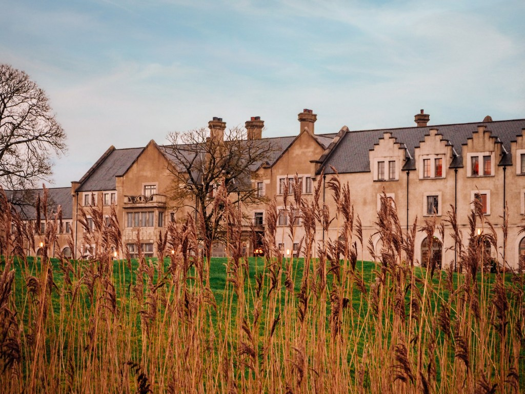 Hotel building of Lough Erne resort viewed through the reeds of Castle Hume Lough lakeshore