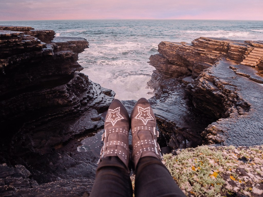 Legs wearing star studded boots hanging over a cliff edge on the Irish coast.